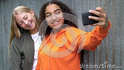 Βίντεο βραχείας κίνησης από όμορφη ξανθιά κοπέλα και έφηβες με μικτές φυλές που χρησιμοποιούν τα έξυπνα τηλέφωνά τους για τα μέσα απόθεμα βίντεο