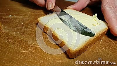 Βούτυρο κηλίδων χεριών στην κηλίδα ορεκτικών ψωμιού φιλμ μικρού μήκους