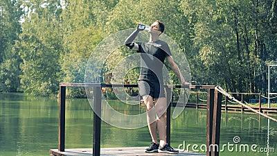 Γέφυρα ποταμών με έναν νεαρό άνδρα που στέκεται σε το και που πίνει με το τεχνητό χέρι του απόθεμα βίντεο