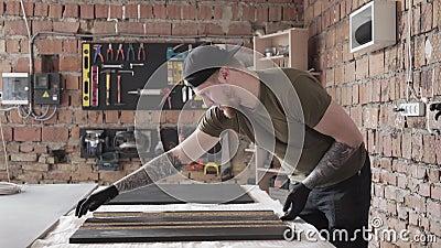 Γενειοφόρος craftman εργασία ικανότητας που στέκεται στον πίνακα στο γκαράζ Μια εργασία ατόμων σε ένα εργαστήριο Ο πίνακας με τα  απόθεμα βίντεο