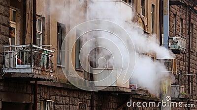 Γκρίζα καπνοδόχος με τον άσπρο καπνό στο κλίμα οικοδόμησης με τα μπαλκόνια και τα παράθυρα απόθεμα βίντεο