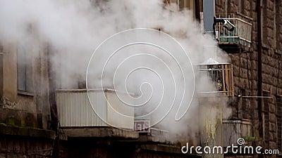 Γκρίζα καπνοδόχος με τον άσπρο καπνό στο κλίμα οικοδόμησης με τα μπαλκόνια και τα παράθυρα 50 fps φιλμ μικρού μήκους