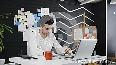 Γραφικός καλλιτέχνης που χρησιμοποιεί την ταμπλέτα γραφικής παράστασης στο γραφείο του φιλμ μικρού μήκους