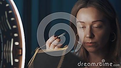 Γυναίκα έλκηθρος γεμίζει τα φρύδια της με μικρό πινέλο μπροστά στο φως των δαχτύλων φιλμ μικρού μήκους