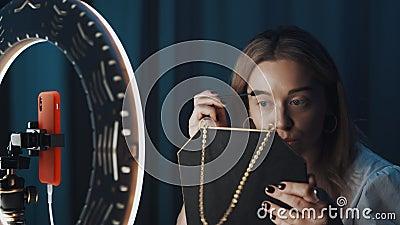 Γυναίκα βυλογράφος γεμίζει τα φρύδια της κρατώντας τον καθρέφτη στα χέρια μπροστά από το φως του δακτυλίου φιλμ μικρού μήκους