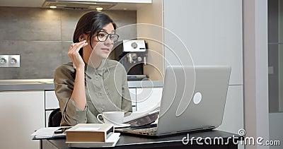 Γυναίκα επιχειρηματίας που μιλάει για επικοινωνία με βίντεο με ακουστικά και φορητό υπολογιστή και σημειώνει σε ένα σημειωματάριο απόθεμα βίντεο