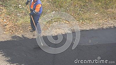 Γυναίκα εργαζόμενος κατά τη διάρκεια του ασφαλτώνοντας δρόμου Βαριά γυναικεία χειρωνακτική εργασία στην κατασκευή απόθεμα βίντεο