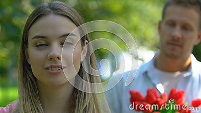 Γυναίκα με αυτοπεποίθηση που αγνοεί τον άνδρα με ένα μπουκέτο από τουλίπες, ανεπανόρθωτη αγάπη φιλμ μικρού μήκους