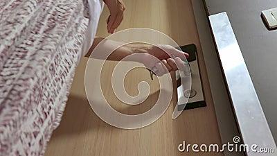 Γυναίκα ξεκλειδώνει την πόρτα του δωματίου του ξενοδοχείου τοποθετώντας μια κάρτα πρόσβασης σε μια ηλεκτρονική κλειδαριά ασφαλεία απόθεμα βίντεο