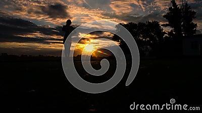 Γυναίκα που αυξάνει τα όπλα στον ουρανό στην παραλία κατά τη διάρκεια του ηλιοβασιλέματος, σε αργή κίνηση απόθεμα βίντεο