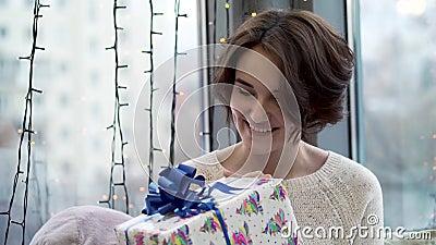 Γυναίκα που εξετάζει το νέο δώρο έτους Η όμορφη νέα γυναίκα στο πουλόβερ με το χαμόγελο και την περιέργεια εξετάζει το δώρο Χριστ απόθεμα βίντεο