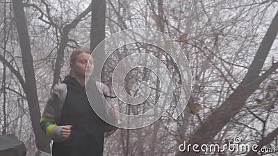 Γυναίκα που τρέχει μέσα στο δάσος στην ομίχλη απόθεμα βίντεο