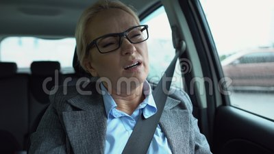 Γυναίκα στο αυτοκίνητο που στριφογυρίζει τον αυχένα της, προσπαθώντας να το τεντώσει, αυχενικοί σπόνδυλοι απόθεμα βίντεο