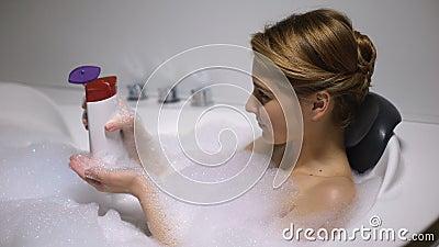 Γυναίκα στο μπάνιο με φυσαλίδες αφρού που εφαρμόζουν πλύσιμο σώματος, διαδικασία ομορφιάς, φρεσκάδα απόθεμα βίντεο