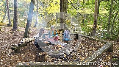 Γυναίκες φίλοι μαγειρεύουν παραδοσιακές τηγανίτες πάνω σε ανοιχτή φωτιά στο στρατόπεδο σε εξωτερικό χώρο κατά τη διάρκεια πεζοπορ απόθεμα βίντεο