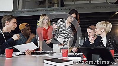 Δημιουργικός θηλυκός αρχηγός ομάδας που στέκεται κοντά γύρω από τον πίνακα και που δίνει την κατεύθυνση στη νέα δημιουργική ομάδα απόθεμα βίντεο