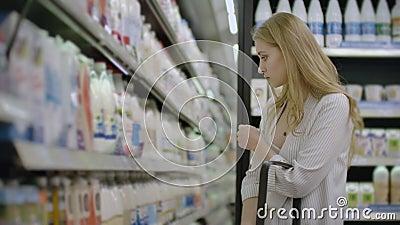 Διαφήμιση, Επιχείρηση, Φαγητό, Έννοια της Υγείας - Γυναίκα σε ένα σούπερ μάρκετ που στέκεται μπροστά από την κατάψυξη και επιλέγε απόθεμα βίντεο