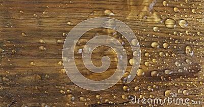 Δυνατός άνεμος φυσάει σταγόνες βροχής από μια καφέ ξύλινη επιφάνεια Κλασικός φυσικός συνδυασμός νερού και ξύλου φιλμ μικρού μήκους