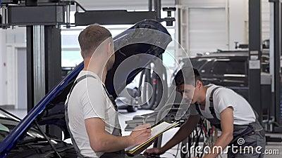 Δυο μηχανικοί συζητούν για την επισκευή κατεστραμμένου αυτοκινήτου στο γκαράζ απόθεμα βίντεο
