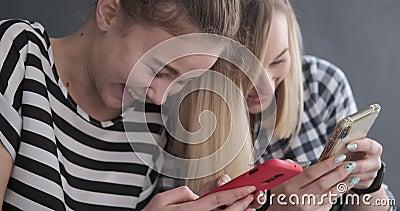 Δύο έφηβη που κουτσομπολεύουν χρησιμοποιώντας τα κινητά τηλέφωνα