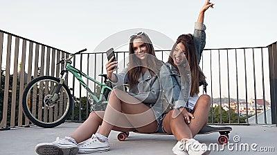 Δύο γυναίκες καλύτερες φίλες αυτοσχεδιάζουν με smartphone όταν κάθονται στο σκέιτμπορντ ενώ περπατούν τη θερινή ηλιόλουστη ημέρα φιλμ μικρού μήκους