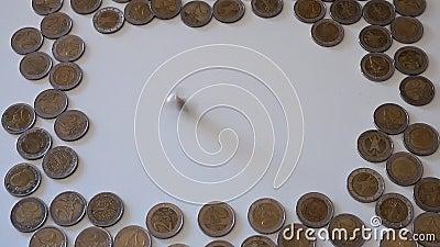 Δύο επίπεδα με πλαίσιο που αποτελείται από δύο κέρματα ευρώ και ένα νόμισμα που κυκλώνεται στο κέντρο φιλμ μικρού μήκους