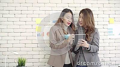 Δύο νέοι ασιατικοί φοιτητές πανεπιστημίου ή συνάδελφοι επιχειρηματιών που πίνουν τον καφέ και που μιλούν τη στην αρχή, διαφορετικ απόθεμα βίντεο
