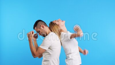 Δύο νεαροί ευτυχισμένοι άνδρες και γυναίκες χορεύουν μαζί σε μπλε φόντο στο στούντιο φιλμ μικρού μήκους