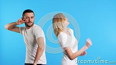 Δύο νεαροί ευτυχισμένοι άνδρες και γυναίκες χορεύουν μαζί σε μπλε φόντο στο στούντιο απόθεμα βίντεο