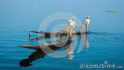 Δύο ψαράδες στην παραδοσιακή στροφή βαρκών inle λίμνη Myanmar απόθεμα βίντεο