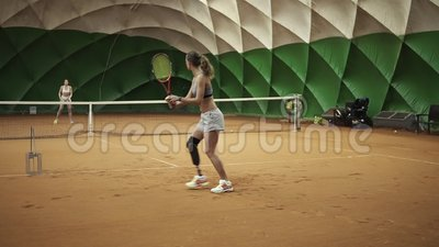 Δύο όμορφα, ψηλά κορίτσια στα αθλητικά ενδύματα και οι στηθόδεσμοι παίζουν την αντισφαίριση indoors Κινούμενη φωτογραφική μηχανή φιλμ μικρού μήκους