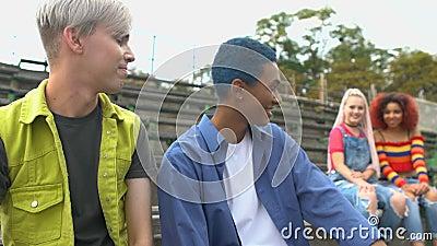 Δύο hipster αρσενικοί φίλοι που κοιτούν με ενδιαφέρον τους όμορφους συμμαθητές τους κοντά φιλμ μικρού μήκους