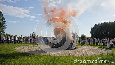 Εθνικοί θερινοί εορτασμοί, πλήθος των ανθρώπων γύρω από τη μεγάλη καπνίζοντας πυρκαγιά κάτω από το σαφή ουρανό στη φύση, μεγάλα ε απόθεμα βίντεο