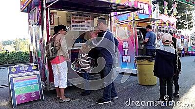 Εισιτήριο οικογενειακής αγοράς στις διασκεδάσεις καρναβάλι δυτικών ακτών φιλμ μικρού μήκους