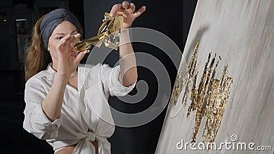 Ελκυστική γυναίκα καλλιτέχνης που εφαρμόζει φύλλα χρυσού στο γραφικό της Ο καλλιτέχνης διακοσμεί εικόνα με ένα μικρό φύλλο χρυσού απόθεμα βίντεο