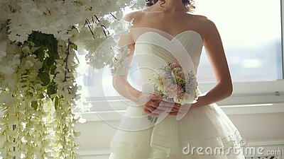 Ελκυστικό πρότυπο στο γαμήλιο φόρεμα με την ανθοδέσμη νυφών ` s φιλμ μικρού μήκους