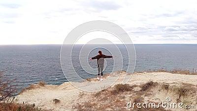 Εναέρια θέα - μια νεαρή γυναίκα αισθάνεται ελευθερία, στεκόμενη στην άκρη ενός γκρεμού πάνω από τον ωκεανό Αθλήτρια σε εξωτερικό  απόθεμα βίντεο