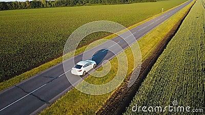 Εναέριος πυροβολισμός της πράσινης επαρχίας και της άσπρης οδήγησης αυτοκινήτων κατευθείαν Ο κηφήνας ακολουθεί το όχημα που οδηγε