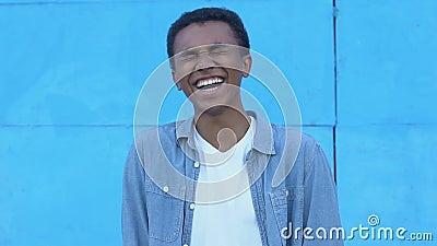 Ενθουσιασμένο αφρο-αμερικανό έφηβο αγόρι που γελάει στο μπλε φόντο, ειλικρινής ευτυχία απόθεμα βίντεο