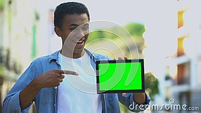 Ενθουσιασμένο μαύρο αγόρι που δείχνει με το δάχτυλο το πράσινο tablet στο χέρι, διαφήμιση απόθεμα βίντεο