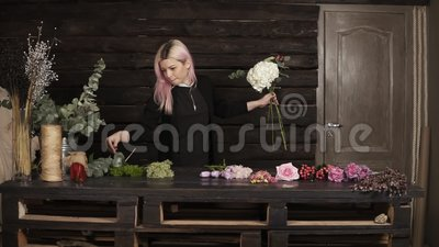 Εντυπωσιακός μπροστινός πυροβολισμός ανθοκόμων στην εργασία Ένα συμπαθητικό κορίτσι συλλέγει τα λουλούδια σε μια σύνθεση indoors φιλμ μικρού μήκους
