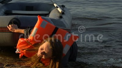 Εξαντλημένο θηλυκό με σωσίβια λέμβο να παίρνει χώρα, το ναυάγιο επέζησε θύμα, τραγωδία φιλμ μικρού μήκους