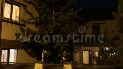 Εξωτερικό ενός κίτρινου ευρωπαϊκού έξυπνου σπιτιού από την κατοικημένη γειτονιά αυτόματα που φωτίζεται σε κάθε δωμάτιο - απόθεμα βίντεο