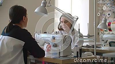 Επαγγελματική Καυκάσια μοδίστρα και νέα μοδίστρα επιλέγουν ύφασμα και μιλάνε ενώ συνεργάζονται με ραπτομηχανή απόθεμα βίντεο