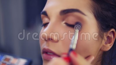 Επαγγελματικός καλλιτέχνης σύνθεσης που εφαρμόζει τη σκιά ματιών για να διαμορφώσει το μάτι που χρησιμοποιεί την ειδική βούρτσα Ο απόθεμα βίντεο