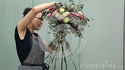 Επαγγελματικός arranger λουλουδιών επιδεικνύει πώς να κάνει μια μικτή ανθοδέσμη λουλουδιών φιλμ μικρού μήκους
