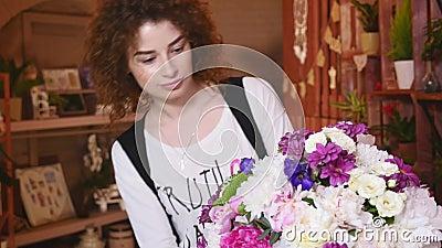Επαγγελματικός arranger λουλουδιών επιδεικνύει πώς να κάνει μια μικτή ανθοδέσμη λουλουδιών απόθεμα βίντεο