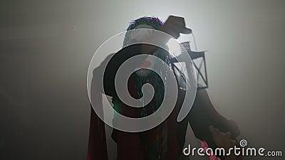 Επιβλαβής κλόουν που προέρχεται από τη σκοτεινή ομίχλη που χορεύει σε αποκριές με έναν λαμπτήρα στα χέρια του που εξετάζουν περίε απόθεμα βίντεο