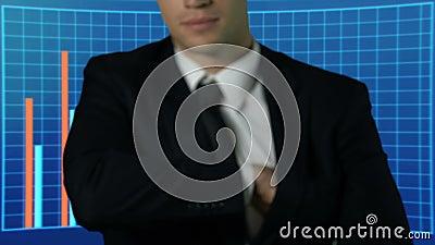 Επιτυχές άτομο στο κοστούμι που παρουσιάζει δέσμη των δολαρίων, επιχειρησιακά διαγράμματα στο υπόβαθρο απόθεμα βίντεο