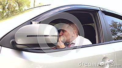 Επιχειρηματίας που τρώει μια Burger συνεδρίαση στο αυτοκίνητο απόθεμα βίντεο